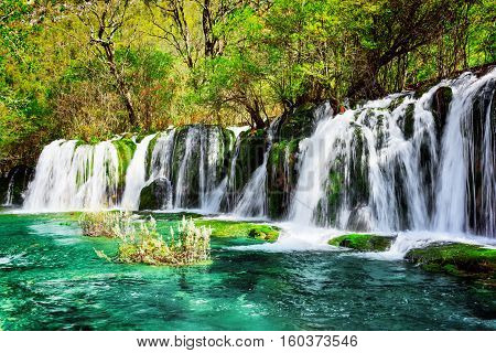 Waterfall And Azure Lake With Crystal Water Among Green Woods