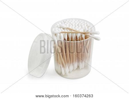 Cotton swabs on a wooden rods in transparent round plastic container on a light background