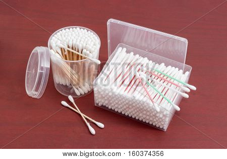 Cotton swabs on a plastic rods in rectangular plastic container cotton swabs on a wooden rods in round plastic container and several cotton buds separately on a red wooden surface