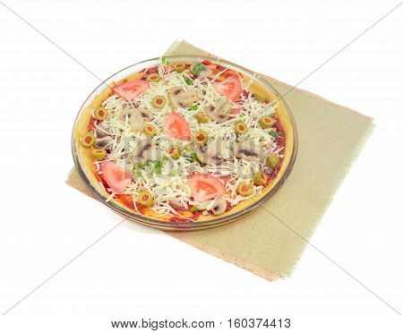 Uncooked round pizza with chicken button mushrooms tomatoes and olives on a glass plate on a textile place mat on a light background