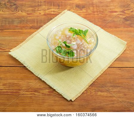 Pork aspic with two twigs of parsley in transparent glass bowl on a table mat on a surface of a old wooden planks