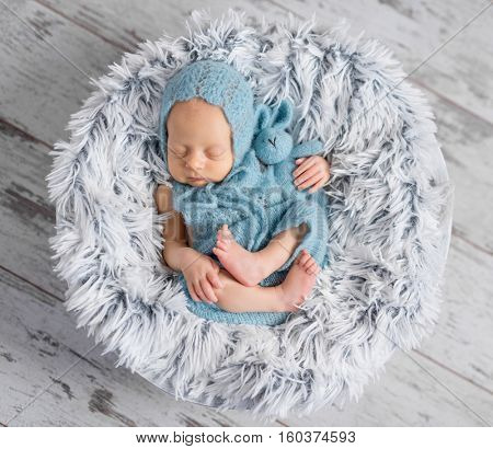 lovely infant in hat and jumpsuit sleeping on round little bed, top view
