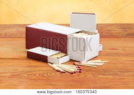 Wooden household safety matches separately and in several cardboard matchboxes of different sizes on a surface old wooden planks closeup
