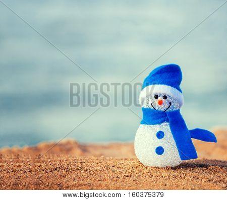 Snowman on sand near sea. Christmas decoration. Vacations