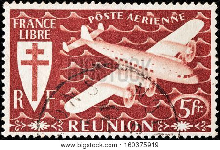 LUGA RUSSIA - NOVEMBER 29 2016: A stamp printed by REUNION shows airplane and Croix de Lorraine. Reunion is an island and region of France in the Indian Ocean circa 1944.