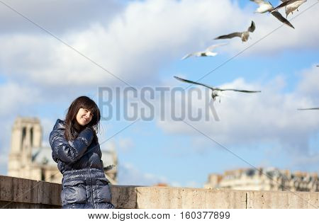 Happy Brunette Girl In Paris Enjoying Windy Spring Day, Sea-gulls Flying At The Background