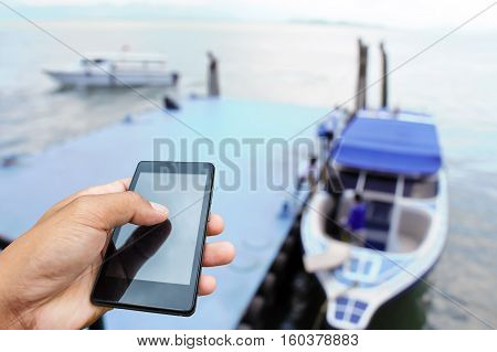 Hand hold and smart phone on port boats closed up hand of man touch screen.