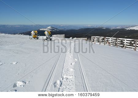 Snowmobile trail in fresh snow snow cannons wooden fence in background and a few mountain peaks in the distance Mt.Kopaonik Serbia