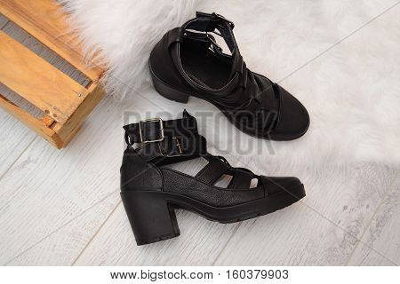 Fashion concept black female shoes with buckles on the wooden box space for text