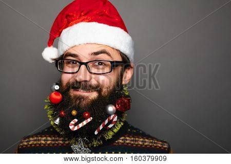 smiley man in santa claus hat over grey background with copy space. Bearded male in glasses with festive beard