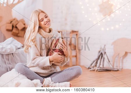 Wonderful time. Happy dreamy young woman sitting cross legged and closing her eyes while holding a Christmas box