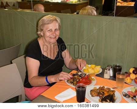 Aged Woman Is Sitting At The Table With Delicious Dishes.