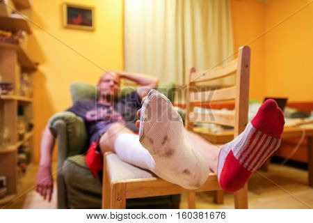 Frustrated man with broken leg on chair
