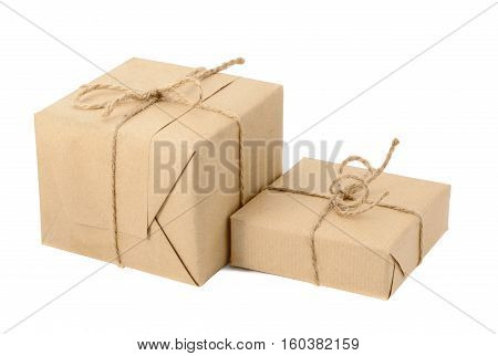 Gift boxes or mail parcels, wrapped with kraft paper and twine, isolated on white background. Craft present