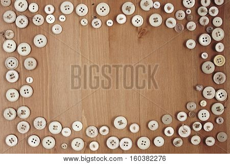 Old vintage buttons frame border on wooden background. Copy space for text