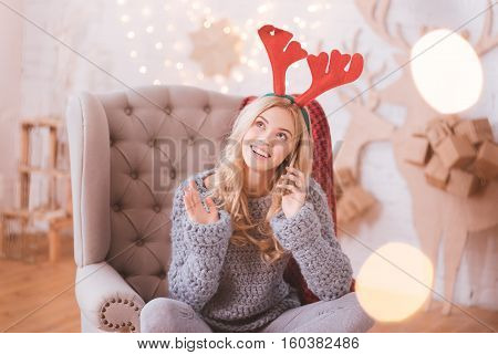 Long distance communication. Happy cute positive woman wearing toy reindeer horns and putting a smartphone to the ear while having a phone conversation