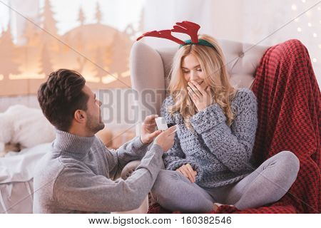 What a surprise. Surprised astounded happy woman sitting cross legged in the armchair and looking at the engagement ring while getting a marriage proposal