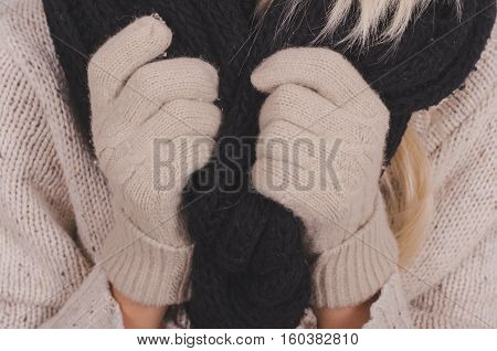 Girl's hands in beige gloves golding a black knitted woolen scarf wintertime and warmth