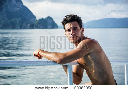 Portrait of young handsome bare-chested brunet man looking away against seascape on a boat or ship, leaning on handrail.