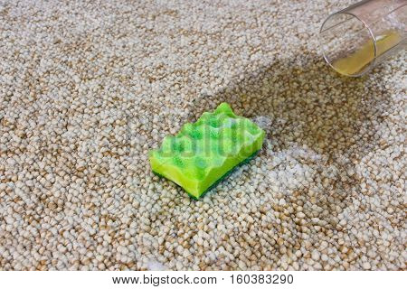 Glass of orange juice fell on carpet. Drink spilled on floor. Sponge and detergent