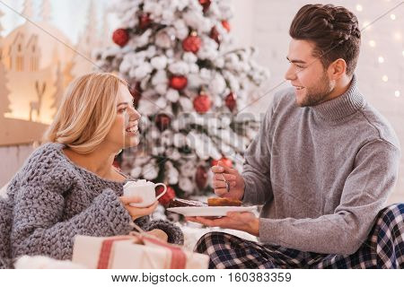 Tasty meal. Happy positive good looking couple sitting on the bed and looking at each other while having breakfast