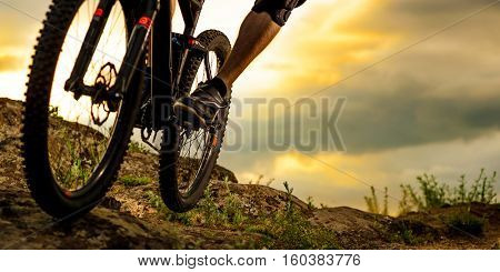 Cyclist Riding the Bike Down Rocky Hill at Sunset. Close up Extreme Sport Concept. Space for Text.