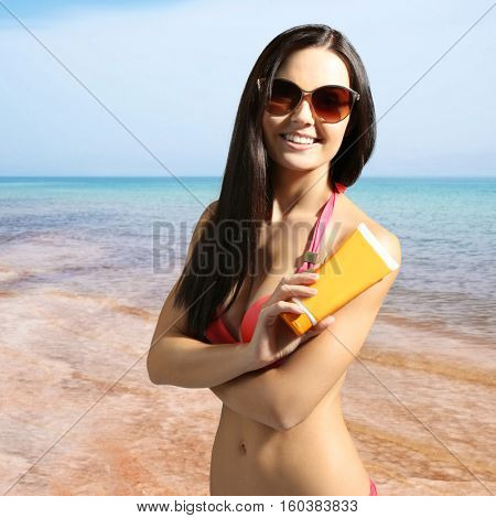Woman with sun protection cream on beach. Skin care concept.