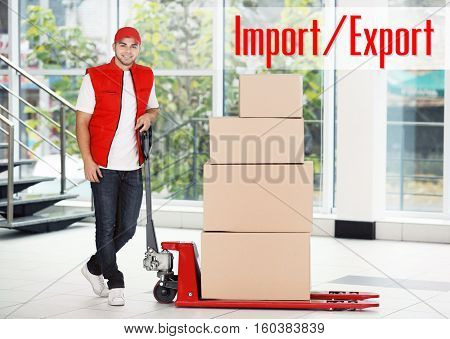 Delivery man in uniform with hand palette truck and cardboard boxes at storehouse. Text IMPORT/EXPORT on background. Wholesale and logistics concept.