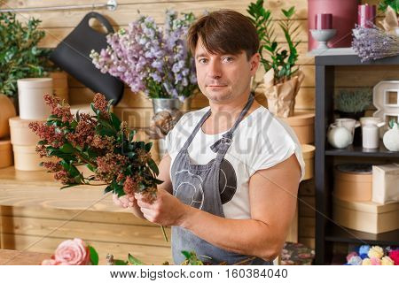 Small business. Male florist making bouquet in flower shop. Man assistant or owner in floral design studio, making decorations and arrangements. Flowers delivery, creating order