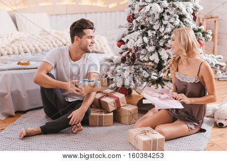 Loving couple. Delighted young happy couple looking at each other and unpacking Christmas gifts while sitting under the Christmas tree