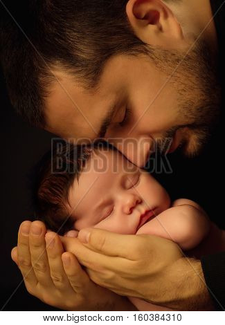 Little 15 days old baby lying securely on his Dad's arms, against a black background.