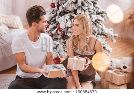 Gifts exchange. Good looking nice optimistic couple sitting in front of the Christmas tree and holding Christmas boxes while giving gifts to each other