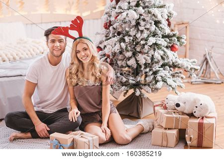 We love winter holidays. Cute positive nice couple sitting under the Christmas tree and being surrounded by Christmas gifts while enjoying their time together