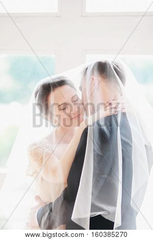 Wedding.Beautiful bride and groom portrait with veil over  face. Stylish Loving wedding couple kissing and hugging