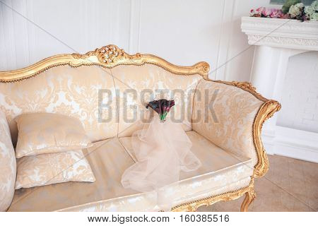 Wedding Bouquet Of  Calla. Bouquet Of Purple Flowers  On The Sofa .veil