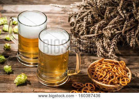 Two tankard beer, wheat spikes, hop on wooden table