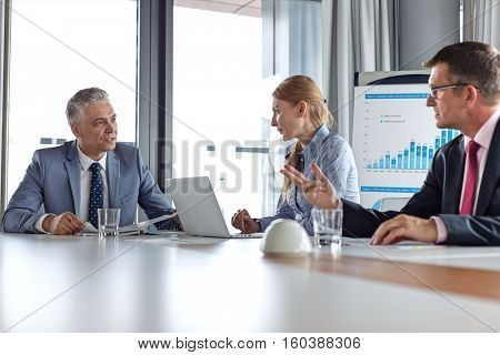 Business people having discussion at table in board room