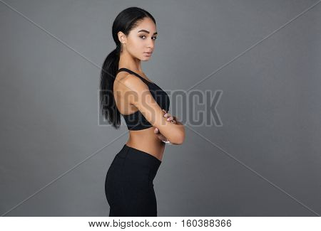 Be earnest. Healthy young sporty woman holding both hands crossed on the chest standing in semi position looking at camera, isolated on grey background
