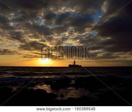 Amazing sunrise from the seashore with low clouds and oil rig in background