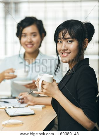 Two young women smiling with coffee in hands