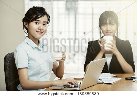 Beautiful young businesswomen working and enjoy drinking coffee