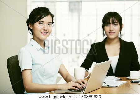 Beautiful young businesswomen working and typing laptop