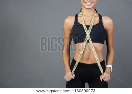 Be attentive. Sporty girl holding yellow centimeter tape around neck crossing it on the chest, standing over grey background