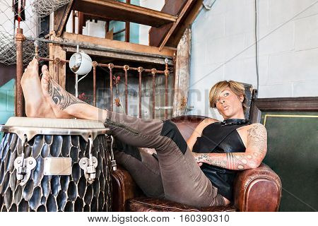 Tattooed girl leans on a leather sofa beside a bongo drum with her legs up on the drum felling relax and funny