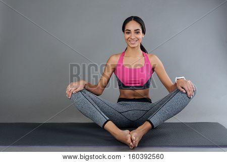 Yoga positions. Positive delighted sportswoman keeping her arms on the legs while sitting on the yoga mat, looking at camera