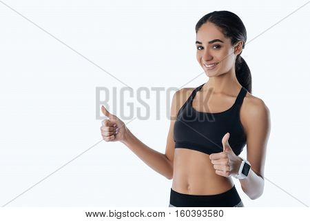 Great results. Happy smiling girl holding both thumbs upwards wearing smart watches, standing in semi position over white background