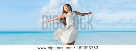Freedom young woman with arms up outstretched to the sky with blue ocean landscape beach background copy space. Banner panorama. Asian girl in white dress dancing carefree in sunset.