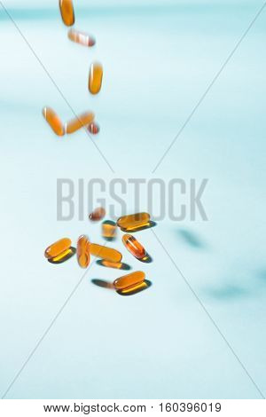 Pills Falling Down. Gel Capsules.  Vitamin A, E, Fish Oil, Primrose Oil, Rice Barn Oil And Other Oil