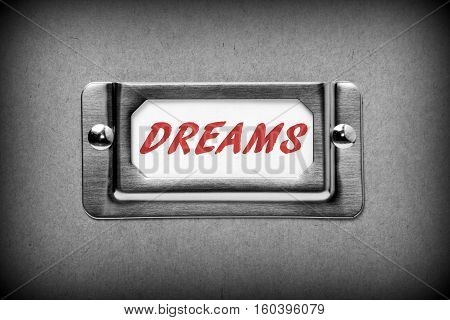 The word DREAMS in red text on a drawer label index card from a filing cabinet as a reminder not to file away your ambitions in a draw and forget them