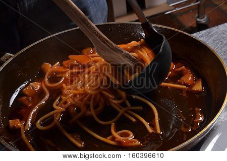 Preparing spaghetti on pan.